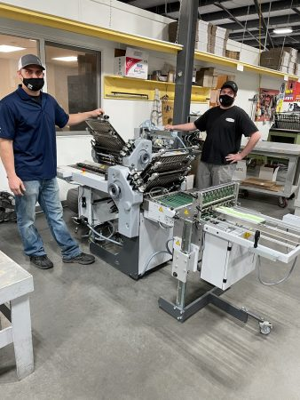Tony Collins, production manager, and Nick Larsen, bindery operator of Peczuh Printing with the newly installed Stahlfolder Ti 36fromHeidelberg.
